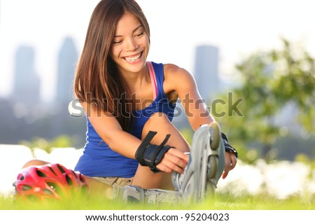 Roller skating woman putting on inline skates for rollerblading. Healthy outdoor workout woman skating outside with montreal city skyline in background. - stock photo