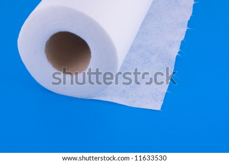 roller towel made of nonwoven fabric with tear-off fibers isolated over blue - stock photo