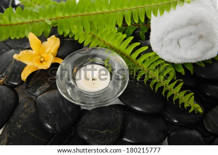 roller towel with green fern and lily , candle on pebbles - stock photo