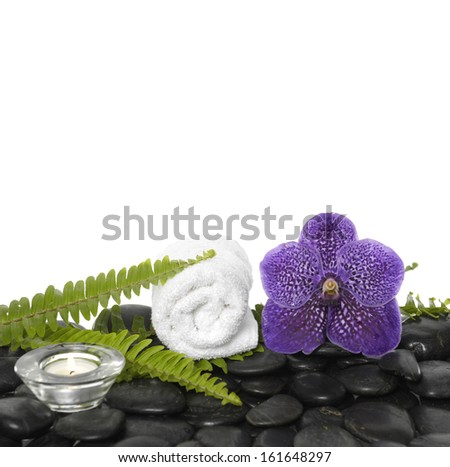 roller towel with green fern and orchid ,candle on black stones - stock photo