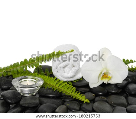 roller towel with green fern and white orchid, candle on pebbles  - stock photo