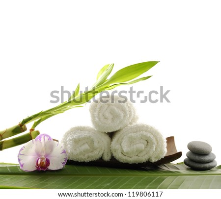 Roller towel with massage oil ,pink orchid and stones ,bamboo on banana leaf - stock photo