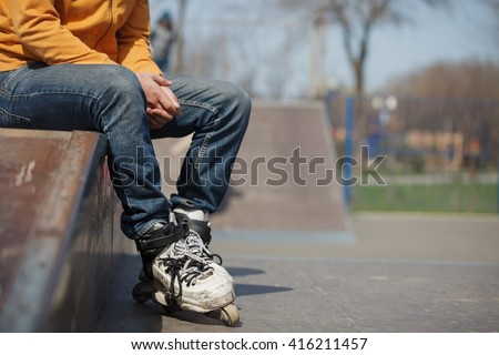 Rollerblader sitting in skatepark wearing professional extreme inline skates made for tricks - grinding and jumping. Dangerous sport popular among youth and teenagers.  - stock photo