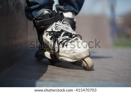 Rollerblader wearing professional extreme inline rollerblades made for tricks - grinding and jumping. Dangerous sport popular among youth and teenagers.  - stock photo