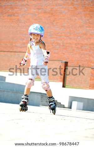 rollerblading  smiling 5 year old girl  going on her in-line skates - stock photo