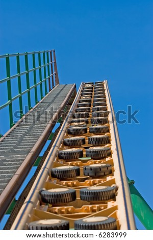 Rollercoaster track against a brilliant blue sky - stock photo