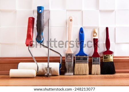 Rollers and brushes to paint on the floor in the room - stock photo