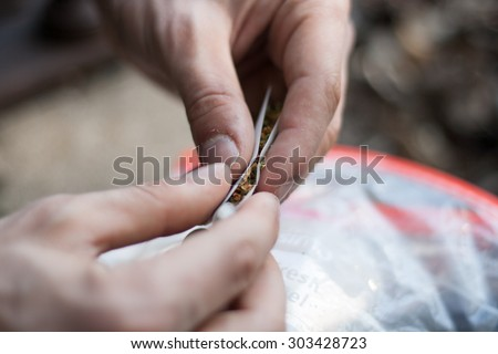 rolling a marijuana cigarette with hands - stock photo
