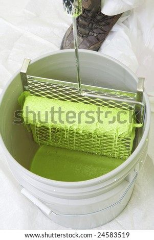 rolling a roller on a screen in a bucket - stock photo