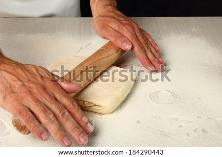 Rolling dough. Making Chocolate Croissants with Puff Pastry - stock photo