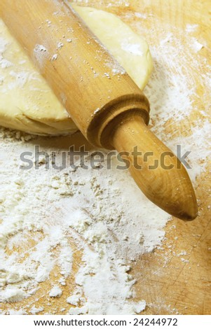 Rolling dough on a floured board, with vintage rolling pin. - stock photo