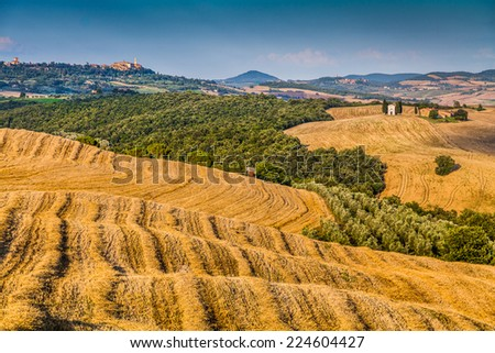 Rolling hills and harvest fields in golden evening light with famous Cappella della Madonna di Vitaleta and the old town of Pienza in the background, Val d'Orcia, Tuscany, Italy - stock photo