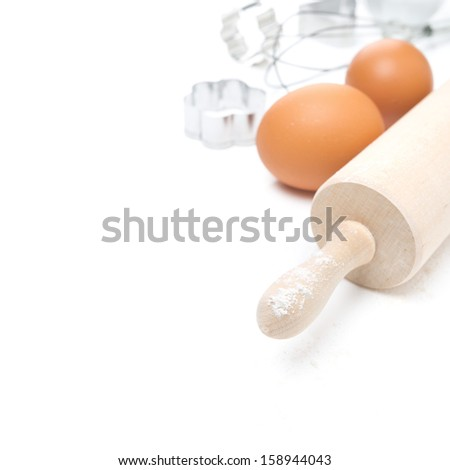 rolling pin, eggs and cookie cutters, selective focus, isolated on white - stock photo