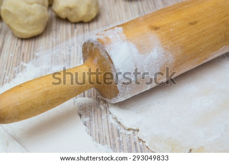 rolling pin with dough and flour on a table. Preparing a baking - stock photo