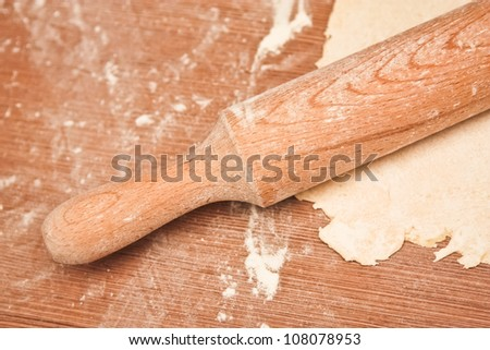 rolling pin with flour and dough on the table - stock photo