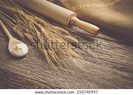 Rolling Pin with Wheat and Spoon with Flour - stock photo