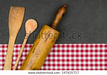 Rolling pin with wooden spoon on a slate plate  - stock photo