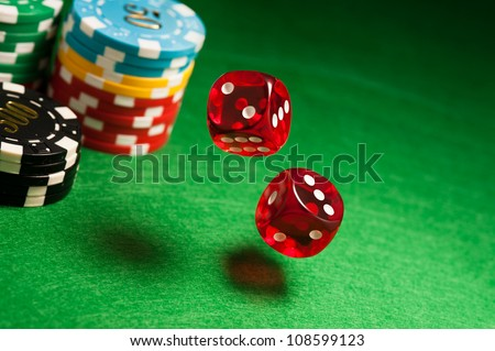 Rolling red dice on a casino table with chips - stock photo