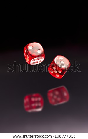 Rolling red dice over black grey background - stock photo