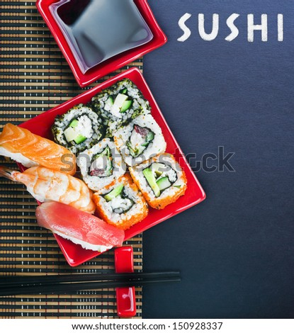 rolls and sushi and chopstick on a black background for text - stock photo