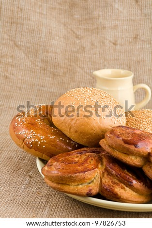 rolls lie on sacking on a background a  jug - stock photo