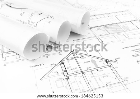 Rolls of architectural house plans and engineering blueprints - stock photo