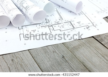 rolls of blueprints and architectural drawings on wooden desk - stock photo