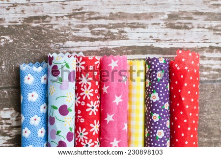 Rolls of colorful patterned fabric - stock photo