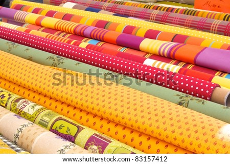 Rolls of colourful fabric at a market - stock photo