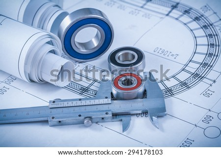 Rolls of construction plans rolling bearings and slide caliper on blueprint industrial concept. - stock photo