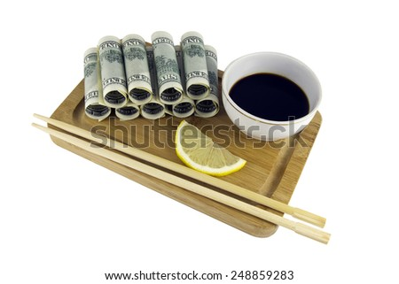 Rolls of dollars, served on the board with soy sauce, lemon and chopsticks - stock photo