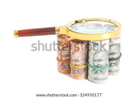 Rolls of Indian Currency Rupee Notes with magnifying glass isolated on white background - stock photo