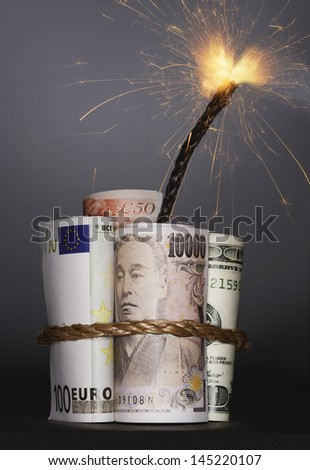 Rolls of money symbolizing dynamite with lit fuse in studio - stock photo