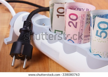 Rolls of polish currency money in electrical extension and disconnected plug, power board, concept of saving money on electricity, energy costs - stock photo