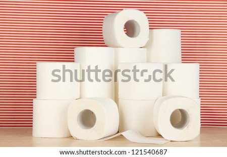 Rolls of toilet paper on striped red background - stock photo