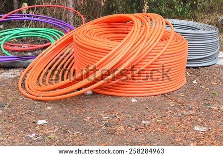 Rolls of underground telephone cable pipes waiting to be laid. - stock photo
