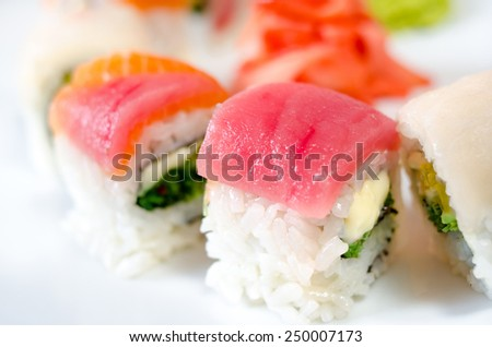 Rolls, sushi and ginger on a white plate and a light background. - stock photo