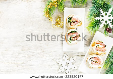 rolls with salmon, spinach and cream cheese on a light woody background. tinting. selective focus on the middle roll - stock photo