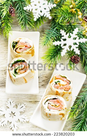 rolls with salmon, spinach and cream cheese on a light woody background. tinting. selective focus on the left roll - stock photo