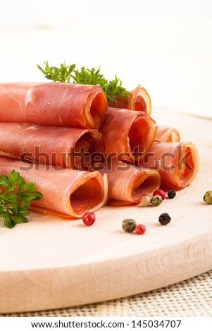 Rolls with smoked ham served with spices on wood - stock photo