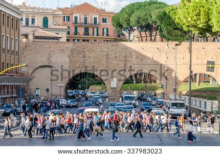 Roma, Italy - October 2015: A large crowd of pedestrians tourists passes through a pedestrian crossing a busy street with traffic cars traffic lights in the center of Rome in Italy - stock photo