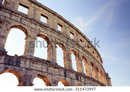 Roman amphitheater arena, theater and coliseum. Classic historical antique building. Tall wall with round arches of an ancient architecture. Travel destination, Istria at Adriatic Sea in Pula, Croatia - stock photo