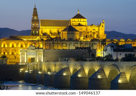 Roman Bridge on Guadalquivir river and Mezquita Cathedral (Great Mosque) at dawn in the city of Cordoba, Andalusia, Spain - stock photo