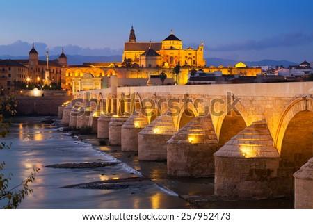 Roman bridge over Guadalquivir river in evening. Cordoba, Spain - stock photo