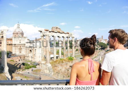 Roman Forum tourists looking at landmark in Rome sightseeing on travel vacation in Rome, Italy. Happy tourist couple, man and woman traveling on holidays in Europe smiling happy. - stock photo