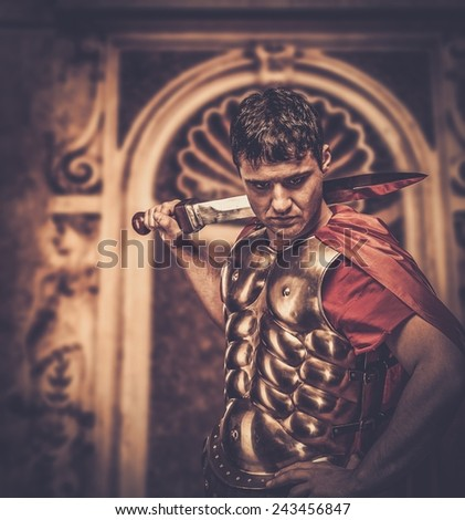 Roman legionary soldier in front of ancient building - stock photo