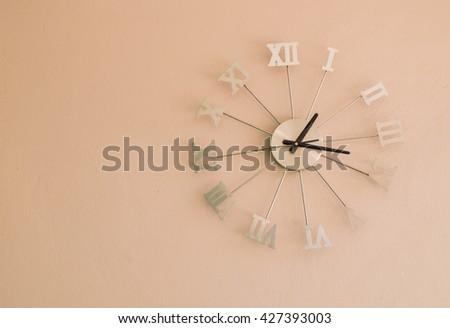 Roman numeral wall clocks on Peach color wall, thirteen o'clock seventeen minutes - stock photo