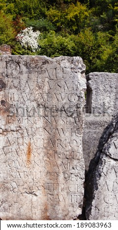 Roman tomb plate with latin inscription in ancient cemetery - stock photo