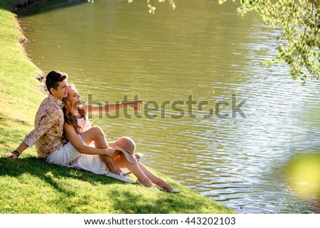 Romance and love. Dating in park. Loving couple sitting together on grass near the lake. - stock photo