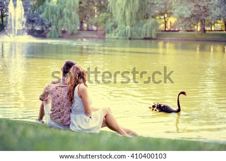 Romance and love. Dating in park. Loving couple sitting together on grass near the lake. filter - stock photo